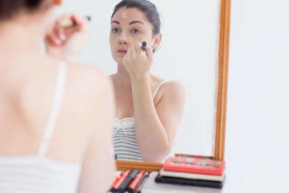 donna che applica il fondotinta allo specchio